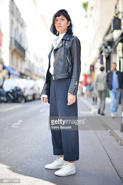 A guest poses wearing a vintage jacket Protagonist shirt Lemaire pants and Common Project shoes after the Lemaire show during Paris Fashion Week SS16...