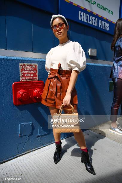 Guest poses wearing a white top, brown skirt and black heels outside the Laquan Smith show during New York Fashion Week on September 08, 2019 in New...