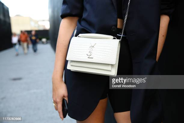 Guest poses wearing a white Yves St Laurent purse outside the Jason Wu show during New York Fashion Week on September 08, 2019 in New York City.