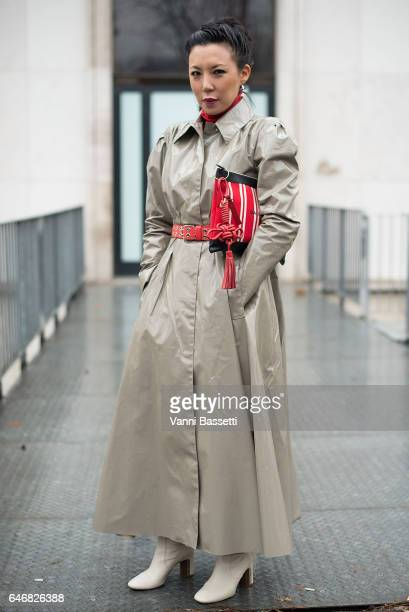 A guest poses wearing an Alessandra Rich trench coat and Balenciaga clutch after the Rochas show at the Palais de Tokyo during Paris Fashion Week...