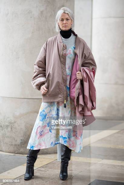 A guest poses wearing an Alpha Industries bomber jacket and a Vetements dress before the Issey Miyake show at the Palais de Tokyo during Paris...
