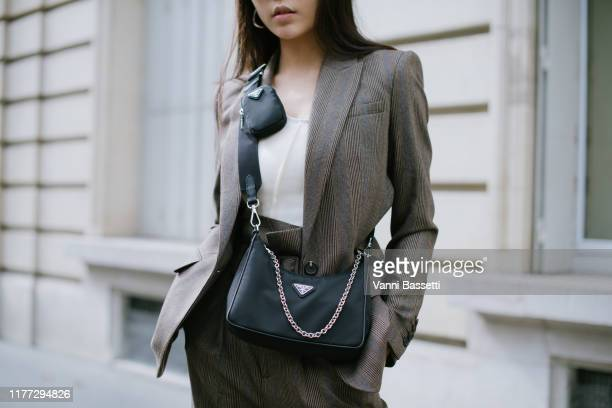 A guest poses wearing an Equipment suit and a Prada bag after the Uma Wang show at the American Cathedral during Paris Fashion Week Womenswear Spring...