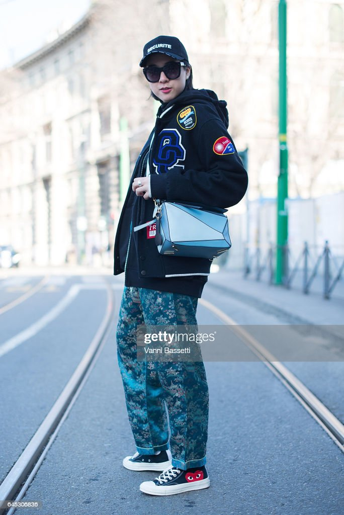 A guest poses wearing an Opening Ceremony jacket, Loewe bag and Comme des Garcons shoes before the Jil Sander show during Milan Fashion Week Fall/Winter 2017/18 on February 25, 2017 in Milan, Italy.