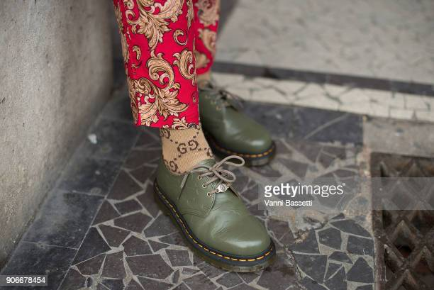 A guest poses wearing Bape X Dr Martens shoes and Gucci socks after the Louis Vuitton show at Place Colette during Paris Fashion week Menswear...