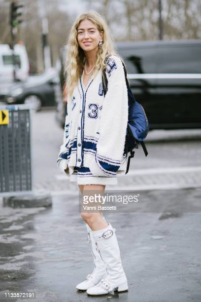 Guest poses wearing Chanel, Miu Miu boots and a Prada bag after the Chanel show at the Grand Palais during Paris Fashion Week Womenswear Fall Winter...