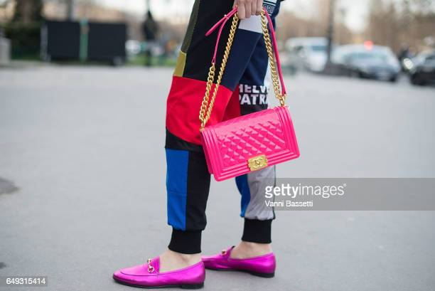 A guest poses wearing Gucci loafers and a Chanel bag after the Shatzy Chen show at the Grand Palais during Paris Fashion Week Womenswear FW 17/18 on...