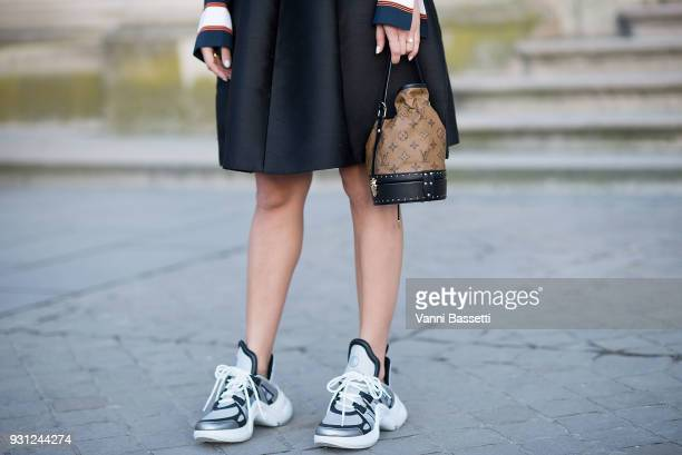 A guest poses wearing Louis Vuitton sneakers before the Louis Vuitton show at the Pyramide du Louvre during Paris Fashion Week Womenswear FW 18/19 on...