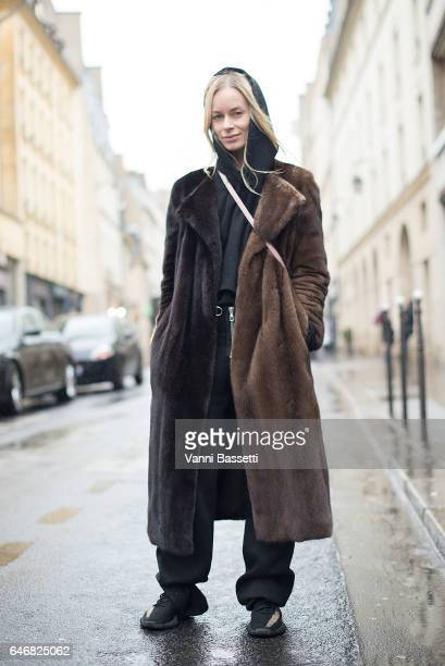A guest poses wearing Yeezy shoes and Loewe bag after the Anne Sofie Madsen show at the Galerie Diana Marquardt during Paris Fashion Week Womenswear...