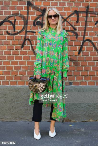 A guest poses with a Balenciaga dress after the Fendi show during Milan Fashion Week Spring/Summer 2018 on September 21 2017 in Milan Italy