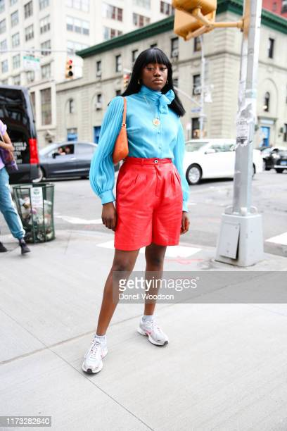 A guest poses with a blue top and red shorts with an orange handbag outside of Spring Studios during New York Fashion Week on September 08 2019 in...
