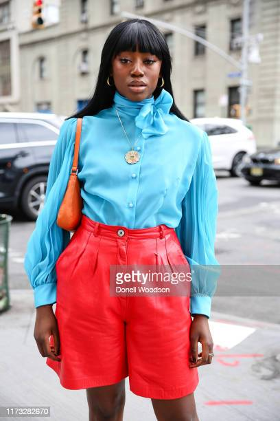Guest poses with a blue top and red shorts with an orange handbag outside of Spring Studios during New York Fashion Week on September 08, 2019 in New...