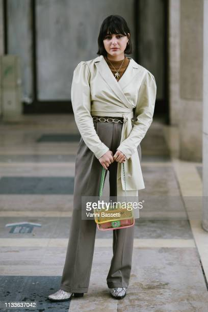 A guest poses with a Chanel bag after the Sacai show at the Palais de Tokyo during Paris Fashion Week Womenswear Fall Winter 2019/2020 on March 04...