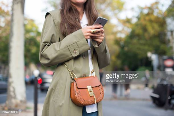 A guest poses with a Chloe bag after the Lemaire show at the Palais de Tokyo during paris Fashion week Womenswear SS18 on September 27 2017 in Paris...