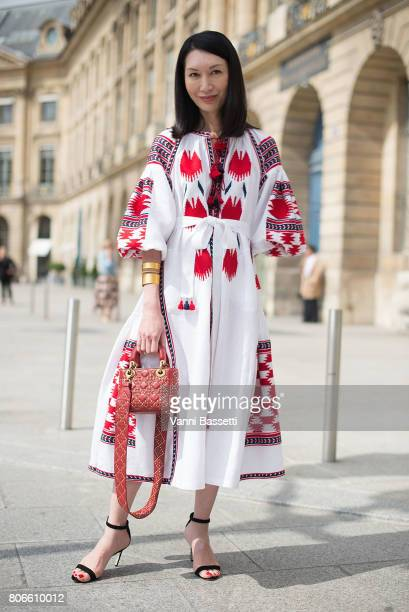 A guest poses with a Dior bag after the Schiaparelli show at Place Vendome during Paris Fashion Week Haute Couture FW 17/18 on July 3 2017 in Paris...