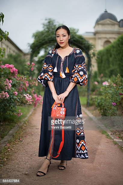 A guest poses with a Dior bag before the Ulyana Sergeenko show at Galerie de la Mineralogie during Paris Fashion Week Haute Couture FW16/17 on July 3...