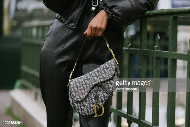 Guest poses with a Dior saddle bag after the Issey Miyake show at the Lycee Carnot during Paris Fashion Week Womenswear Fall/Winter 2020/2021 on...