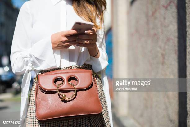 A guest poses with a JW Anderson bag after the Fendi show during Milan Fashion Week Spring/Summer 2018 on September 21 2017 in Milan Italy