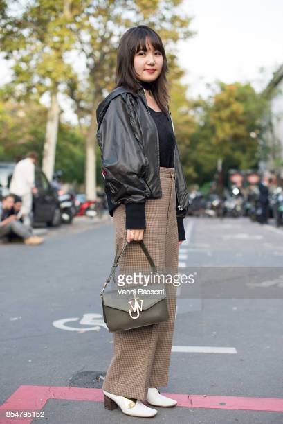 A guest poses with a JW Anderson bag after the Lemaire show at the Palais de Tokyo during paris Fashion week Womenswear SS18 on September 27 2017 in...