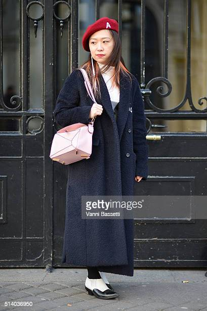 A guest poses with a Loewe bag after the John Galliano show at the Lycee Carnot during Paris Fashion Week FW 16/17 on March 6 2016 in Paris France