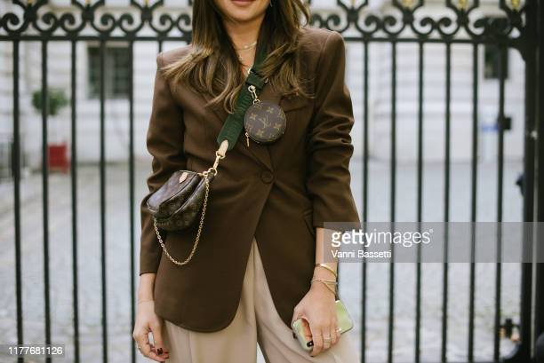 A guest poses with a Louis Vuitton bag after the Altuzarra show at the Hotel Potocki during Paris Fashion Week Womenswear Spring Summer 2020 on...