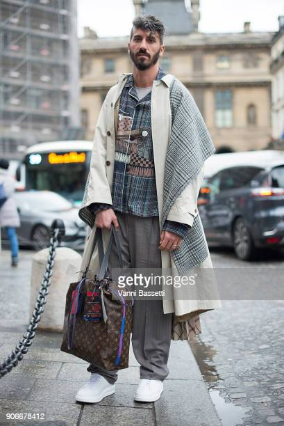A guest poses with a Louis Vuitton bag after the Louis Vuitton show at Place Colette during Paris Fashion week Menswear FW18/19 on January 18 2018 in...