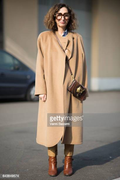 A guest poses with a Prada bag before the Gucci show during Milan Fashion Week Fall/Winter 2017/18 on February 22 2017 in Milan Italy