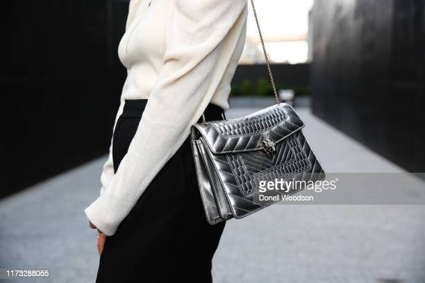 Guest poses with a silver handbag outside the Jason Wu show during New York Fashion Week on September 08, 2019 in New York City.