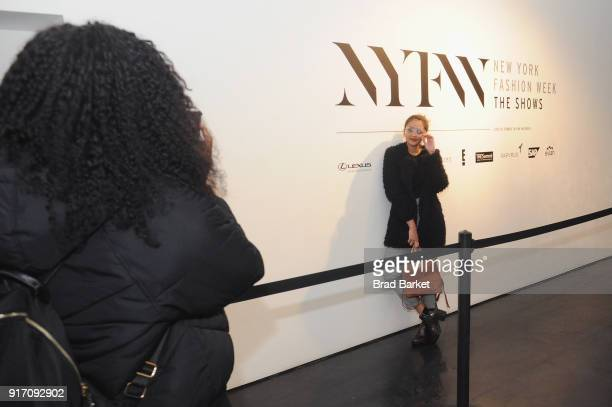 A guest poses with signage in the lobby during IMG NYFW The Shows at Spring Studios on February 11 2018 in New York City