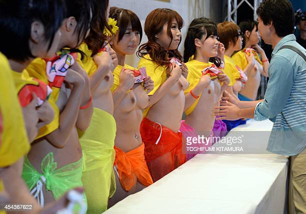 A guest prepares to squeeze the breasts of nine Japanese porn actresses in Tokyo on August 30 during a charity event loosely translated as 'Boob Aid'...