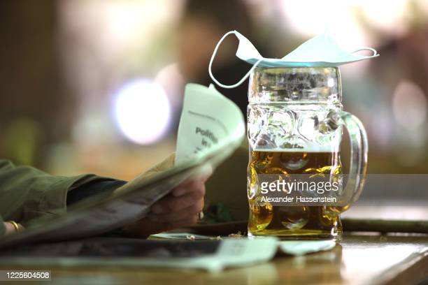 Guest reads a newspaper with a mug of beer at the beer garden of the Hofbräukeller park on the first day beer gardens were allowed to reopen in...