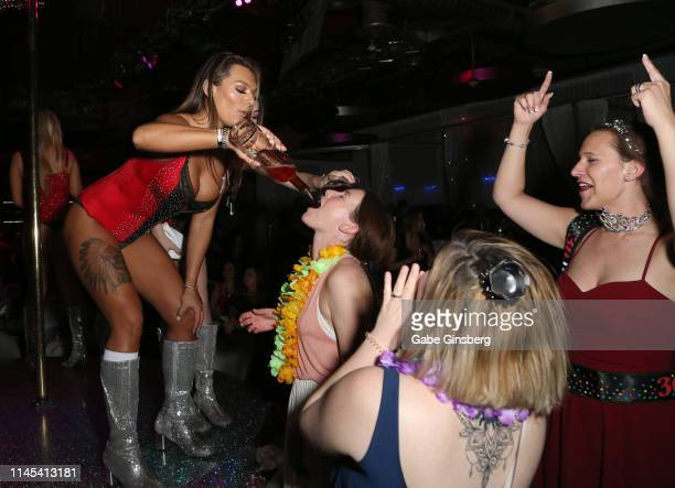 A guest receives a shot from waitresses on stage during Larry Flynt's Hustler Club The Gamer Convention celebration at Larry Flynt's Hustler Club on...