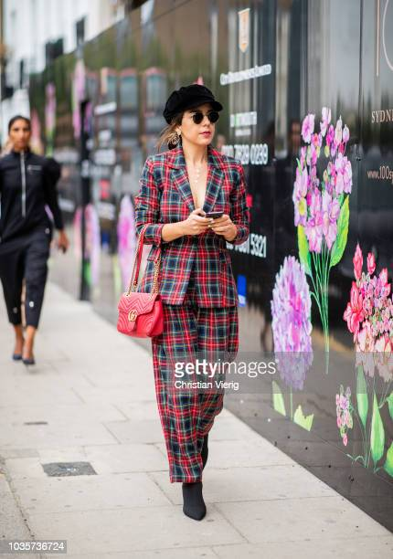 A guest red navy checked suit is seen outside Natasha Zinko during London Fashion Week September 2018 on September 18 2018 in London England
