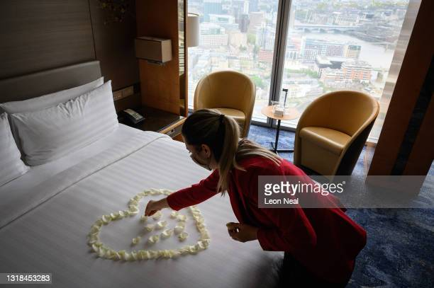 Guest Relations Manager Franziska Frauscher creates a heart from rose petals in a room at the Shangri-la Hotel at The Shard as it re-opens to the...