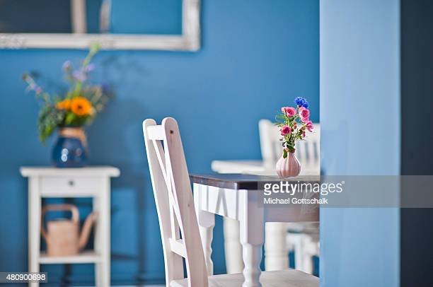 Guest room in a cafe with white furniture and white wooden chairs and tables and a bunch of flowers on July 15 2015 in Berlin Germany