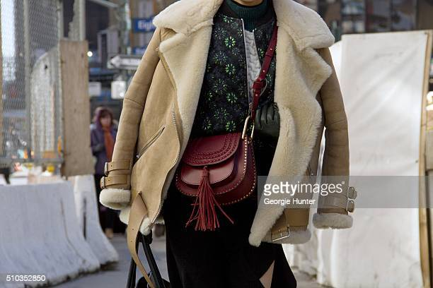 Guest seen at Skylight at Moynihan Station outside the Hood By Air show wearing coat with fur lining and red leather bag with tassle during New York...