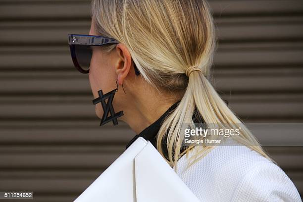 Guest seen at Skylight Clarkson Sq outside the Ralph Lauren show wearing white suit white leather clutch bag sunglasses and statement earring during...
