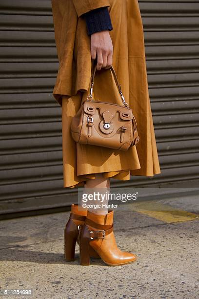 Guest seen at Skylight Clarkson Sq outside the Ralph Lauren show wearing suede coat tan leather bag and boots during Women's Fall/Winter 2016 on...