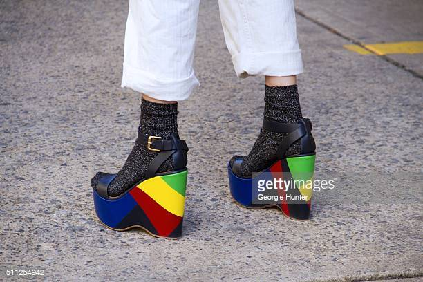 Guest seen at Skylight Clarkson Sq outside the Ralph Lauren show wearing white pants and platform shoes with multicolor wedge worn with socks during...