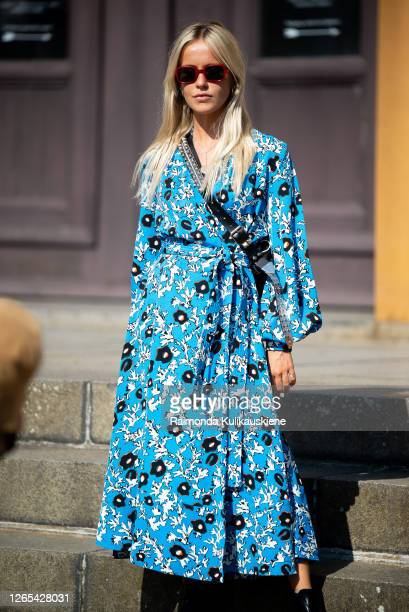Guest seen outside Remain Birger Christensen wearing blue dress with flowers during Copenhagen fashion week SS21 on August 11, 2020 in Copenhagen,...