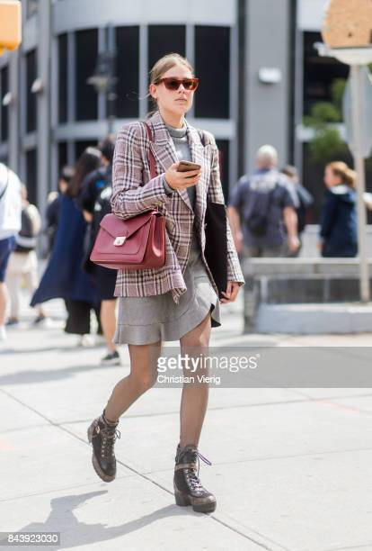 A guest seen wearing checked blazer jacket turtleneck skirt tights black boots in the streets of Manhattan outside Desigual during New York Fashion...