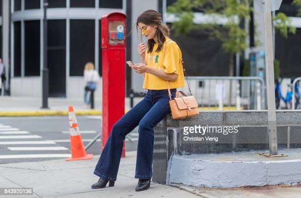 A guest seen wearing flared denim jeans yellow tshirt in the streets of Manhattan outside Desigual during New York Fashion Week on September 7 2017...