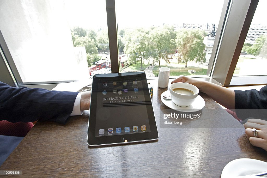 A guest shows an Apple Inc. iPad to a friend at the InterContinental Hotel in London, U.K., on Tuesday, May 25, 2010. The popularity of the iPad will spur a sixfold increase in industrywide shipments of tablet computers by 2014, research firm IDC said. Photographer: Chris Ratcliffe/Bloomberg via Getty Images