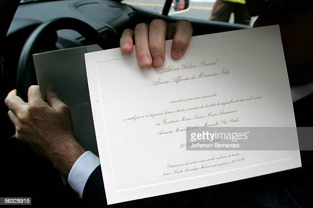 A guest shows his invitation to photographers outside the grounds of the Maria Luisa and Oscar Americano Foundation art museum as he arrives to...