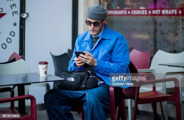 A guest sitting in a cafe wearing wool hat blue jacket baggy jeans boots The North FAce bag during London Fashion Week Men's January 2018 on January...