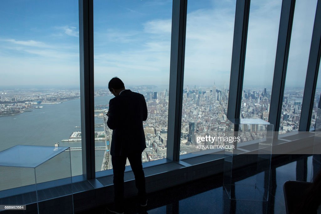 A guest stands next to the window before a press conference before announcing the next soccer 2026 World Cup in North America on April 10, 2017 at the One World Trade Center in New York. The United States, Mexico and Canada announced a joint bid to stage the 2026 World Cup on Monday, aiming to become the first three-way co-hosts in the history of FIFA's showpiece tournament. /