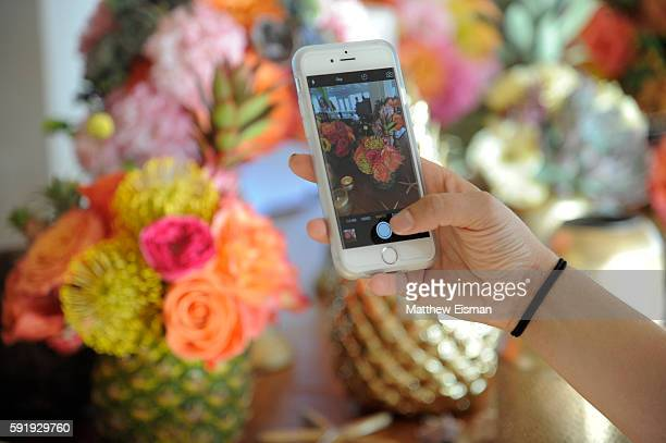 A guest takes a cell phone photo of floral arrangements at B Floral's Evening of Florals Ocean Air and Cocktails with Bronwen Smith at Bridgehampton...