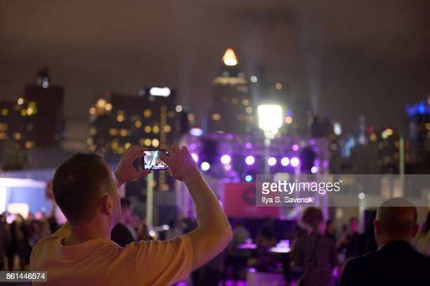 A guest takes a photo at the Food Network Cooking Channel New York City Wine Food Festival presented by CocaCola Rooftop Iron Chef Showdown Battle...