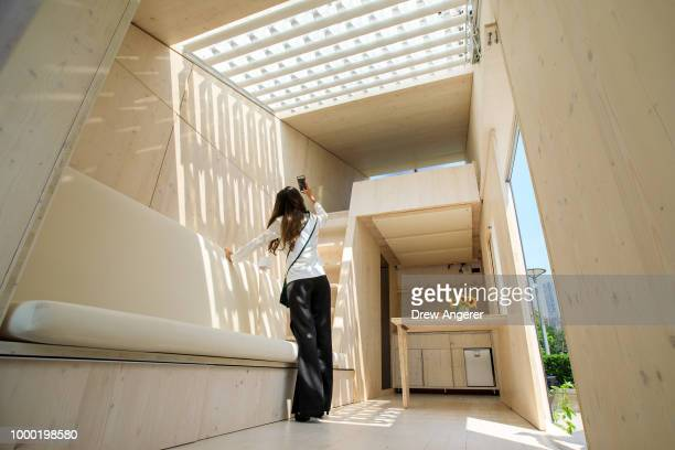 A guest takes a photo inside an ecological living module a 22 square meter 'tiny house' at the United Nations Plaza July 16 2018 in New York City...