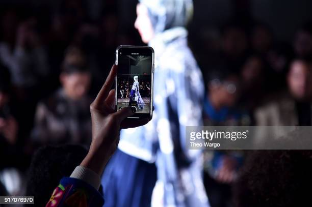 A guest takes a photo of the Vivi Zubedi show during New York Fashion Week The Shows at Industria Studios on February 11 2018 in New York City