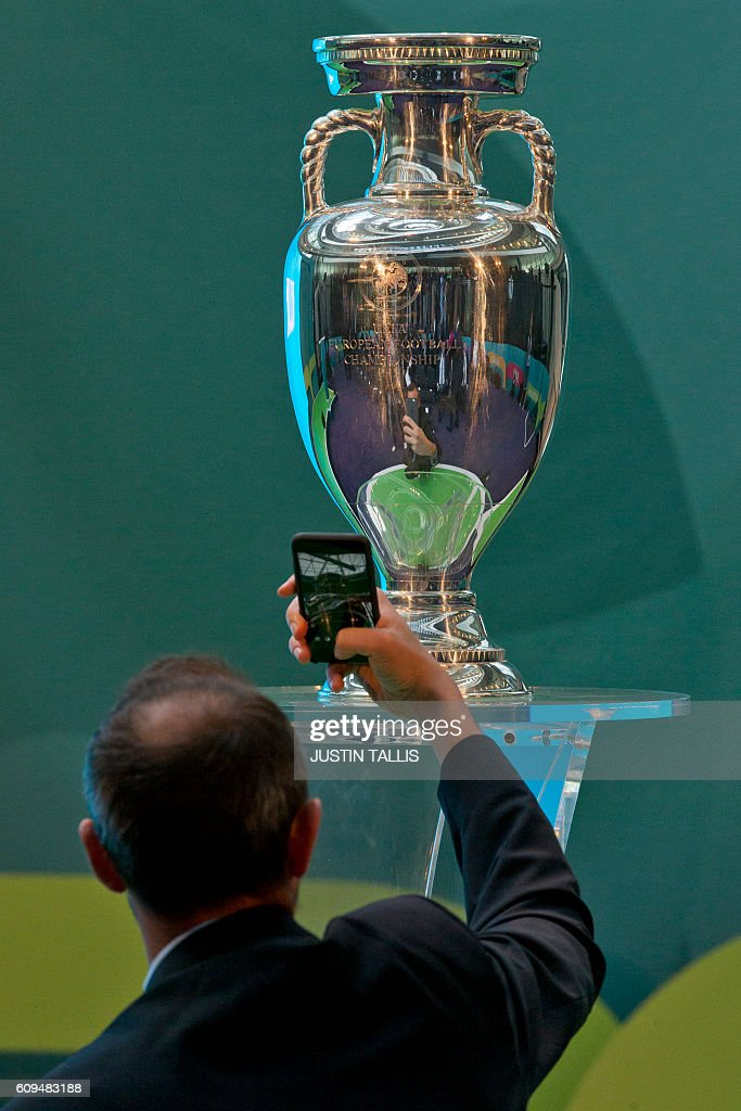 A guest takes a photograph of the UEFA European Championship football competition trophy at a launch event for the 2020 euros logo in London on September 21, 2016. The 2020 UEFA European Championship will see matches hosted in 13 cities across Europe, with the semi-finals and final staged at Wembley Stadium in London in July 2020. / AFP / JUSTIN